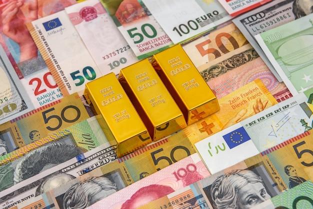 Ingots van goud op kleurrijke bankbiljetten close-up