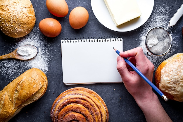 Ingrediënten bakken voor bloem en roggebakkerijproducten. vers brood, stokbrood, broodjes en open receptenboek op een zwarte schoolbordachtergrond