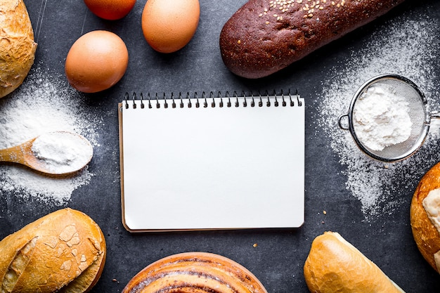 Ingrediënten bakken voor bloem en roggebakkerijproducten. vers knapperig brood, stokbrood, broodjes op een zwarte bordachtergrond.