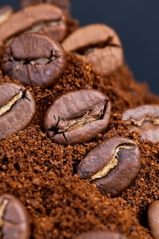 Ingrediënten die kunnen worden gebruikt om een warme, verkwikkende koffiedrank, koffiebonenpoeder en hele koffiebonen te maken, gebrande bonen worden op gemalen koffie geplaatst