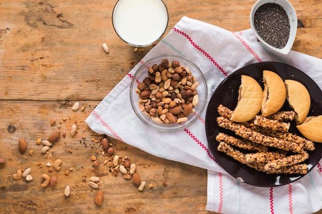 Ingrediënten; droge vruchten; koekjes en mueslireep op houten lijst met servet