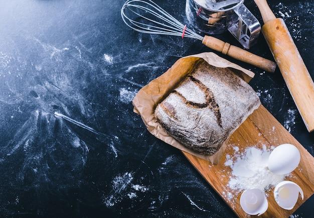 Ingrediënten en gebruiksvoorwerp voor het bakken op het zwarte bord, bovenaanzicht