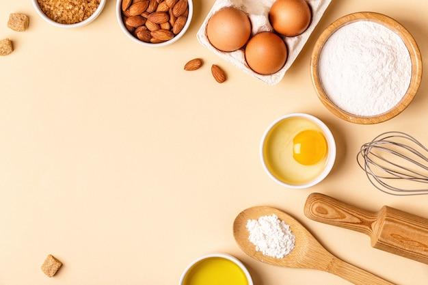 Ingrediënten en gebruiksvoorwerpen voor het bakken op een pastelkleurige achtergrond, bovenaanzicht.