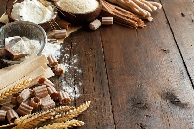 Ingrediënten en gebruiksvoorwerpen voor het maken van pasta op een houten tafel