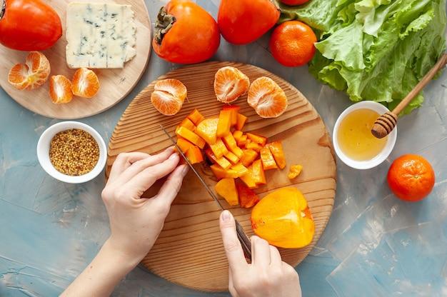 Ingrediënten en het proces van het maken van een vitaminesalade met kaki, mandarijnen en blauwe kaas. stap voor stap. vrouw snijdt persimmon op een ronde houten plank. uitzicht van boven.