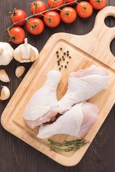 Ingrediënten en rauwe kippentrommelstokken op snijplank op houten tafel