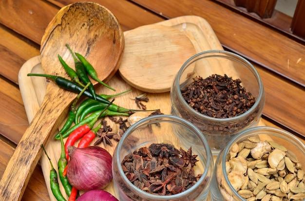 Ingrediënten koken. specerijen en kruiden met ui en knoflook op houten bord