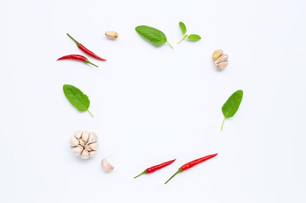 Ingrediënten kruid en specerijen, heilige basilicum, chili en knoflook op wit.