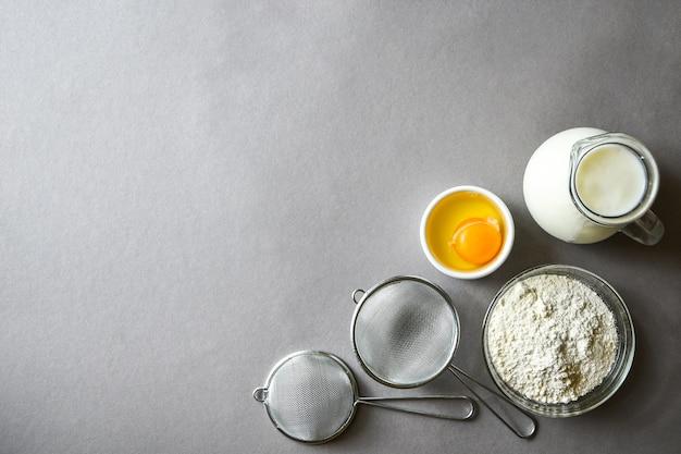 Ingrediënten om pannekoekenkoekjes op grijze achtergrond te maken. kopieer ruimte voor tekst. achtergrondrecept bakken