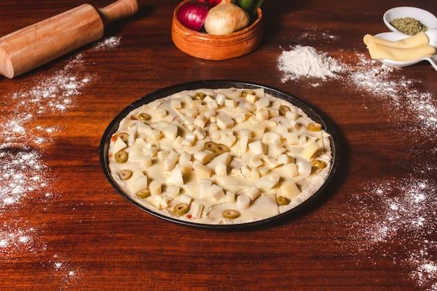 Ingrediënten op een houten tafel geplaatst met een pizza klaar om te verwarmen.