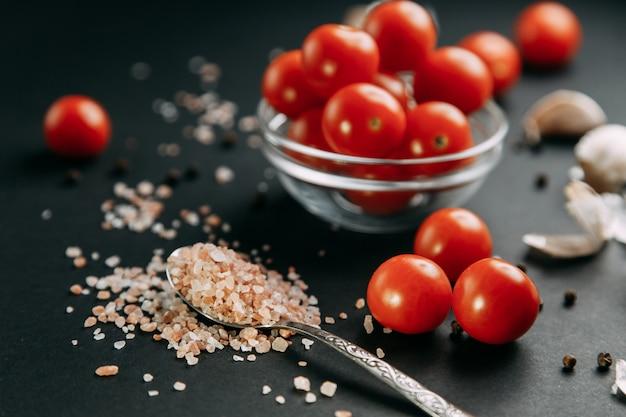 Ingrediënten op zwarte achtergrond. cherry tomaten met knoflook en zout in kommen.