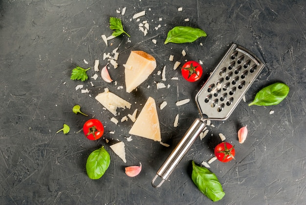 Ingrediënten uit de italiaanse keuken. geraspte parmezaanse kaas en een stuk, met een rasp, basilicumbladeren, knoflook en kerstomaatjes op een donkere betonnen tafel. bovenaanzicht copyspace