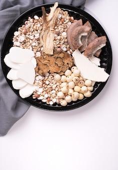 Ingrediënten van four tonics soup, four herb flavour soup. taiwanese traditionele gerechten met job's tranen, kruiden, varkensdarmen op witte achtergrond