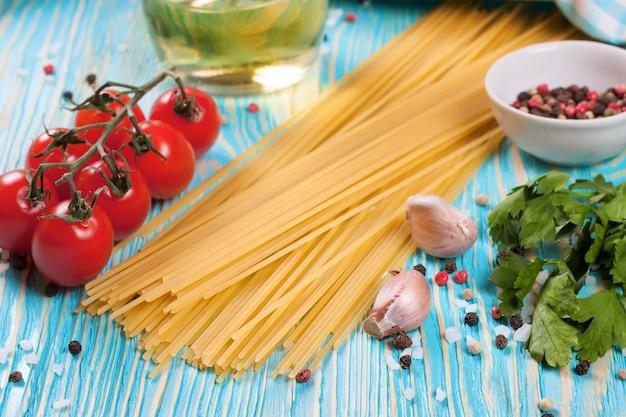 Ingrediënten van pasta, blauw geruite handdoek en kruiden op blauwe houten oppervlak.