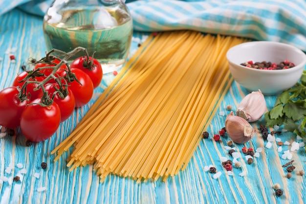 Ingrediënten van pasta, blauwe geruite handdoek en kruiden op blauwe houten ondergrond.