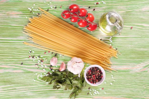 Ingrediënten van pasta en kruiden op groene houten ondergrond. bovenaanzicht.