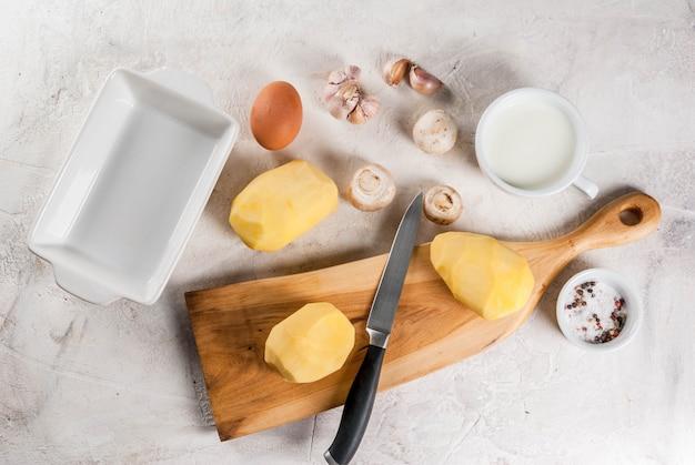 Ingrediënten voor aardappelgratin op stenen tafel