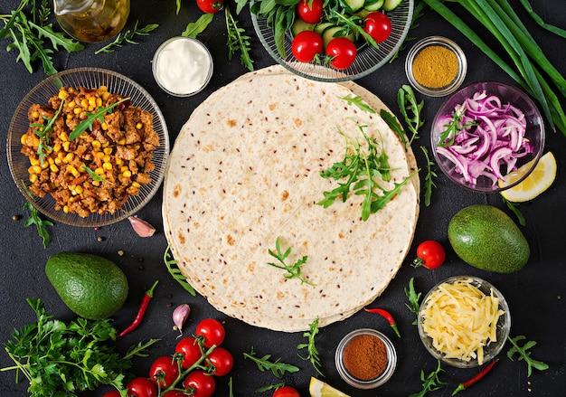 Ingrediënten voor burrito's wraps met rundvlees en groenten op zwarte achtergrond. bovenaanzicht