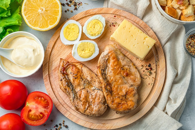 Ingrediënten voor caesar salade op een snijplank op een grijs bureau