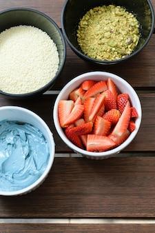 Ingrediënten voor cake, aardbeien, blauwe botercrème, witte chocolade hagelslag en gehakte pistachenoten (bovenaanzicht).