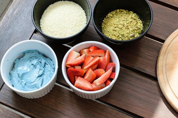 Ingrediënten voor cake, aardbeien, blauwe botercrème, witte chocolade hagelslag en gehakte pistachenoten.