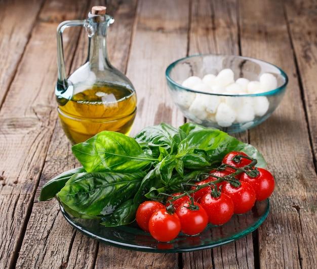 Ingrediënten voor caprese salade. mozarella, basilicum, tomaten, olijfolie
