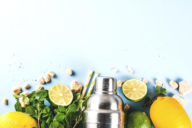 Ingrediënten voor cocktailmojito of limonade - citroen, limoen, munt, suiker, met shaker en cocktailrietjes. op een lichtblauw copyspace bovenaanzicht