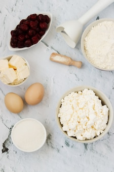 Ingrediënten voor de bereiding van cake met kersen: meel, bakpoeder, eieren, kwark, boter, suiker en kers