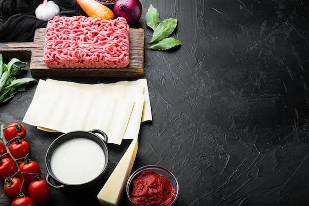 Ingrediënten voor de bereiding van lasagne. tomaten, saus, bechamel-set, op zwarte stenen achtergrond, met kopieerruimte voor tekst