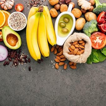 Ingrediënten voor de gezonde voedselselectie. het concept gezonde voedselopstelling op donkere concrete achtergrondexemplaarruimte.