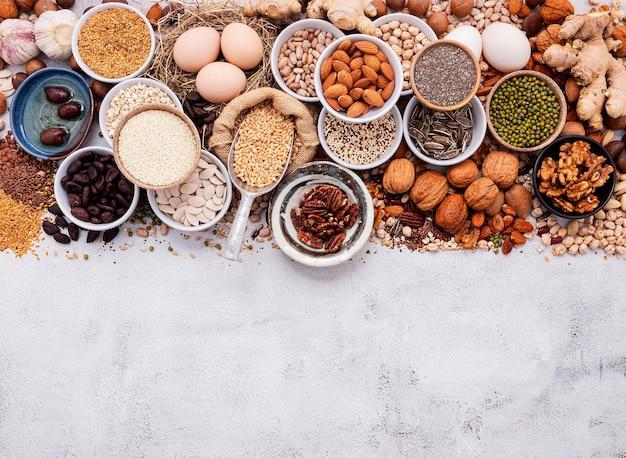 Ingrediënten voor de selectie van gezonde voedingsmiddelen. het concept van superfoods opgezet op witte armoedige betonnen achtergrond met kopieerruimte.