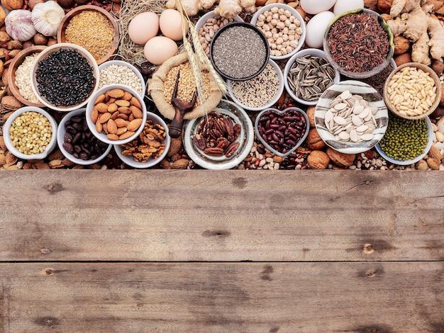 Ingrediënten voor de selectie van gezonde voedingsmiddelen in keramische kom. het concept van superfoods opgezet op witte armoedige houten achtergrond met kopieerruimte.