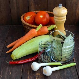 Ingrediënten voor de stoofschotel van groenten (courgette, wortelen, tomaten, kruiden, knoflook, chili)