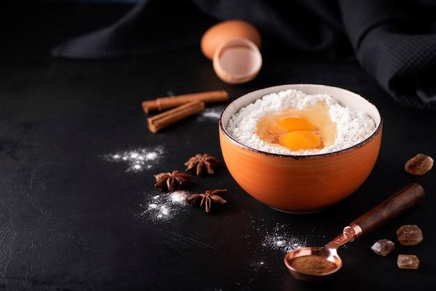 Ingrediënten voor de taart - bloem, eieren, suiker, kaneel in een oranje kom op een donkere achtergrond