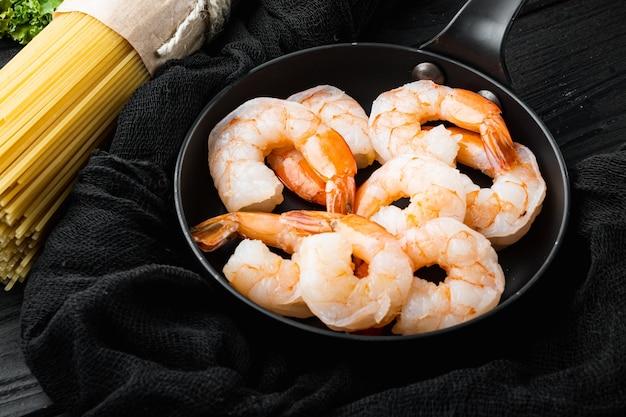 Ingrediënten voor deegwaren met zeevruchten. garnalen, spaghetti, parmezaan, ricotta set, op koekenpan, op zwarte houten tafel