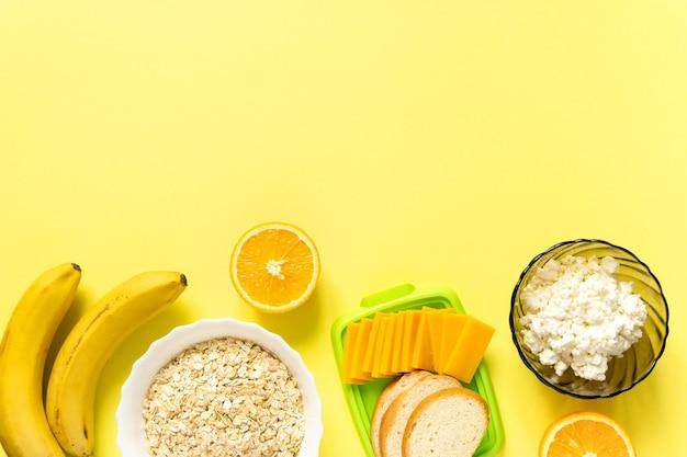 Ingrediënten voor een gezond ontbijt. havermout, zuivelproducten en fruit op gele ondergrond, bovenaanzicht.