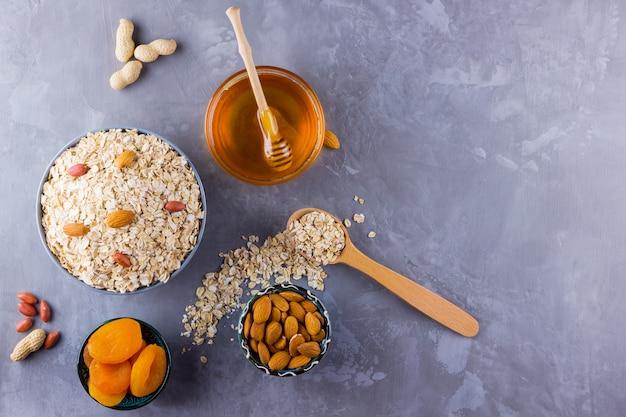 Ingrediënten voor een gezond ontbijt, noten, havermout, honing, gedroogde abrikozen, amandelen, pinda's. concept van natuurlijk biologisch voedsel