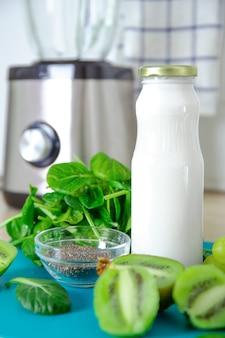 Ingrediënten voor een groene smoothie. turquoise achtergrond van banaan, spinazie, chiazaden, kokosmelk in een glazen pot, avocado, druiven. detox, smoothie recept voor een gezond voedingspatroon.