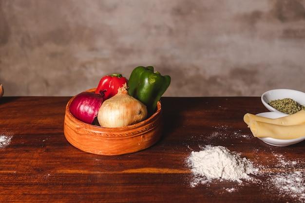 Ingrediënten voor een pizza op een houten tafel geplaatst.