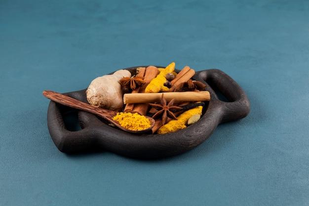 Ingrediënten voor een populaire indiase drank karak-thee of masala-chai in houten serveerschaal op blauw.