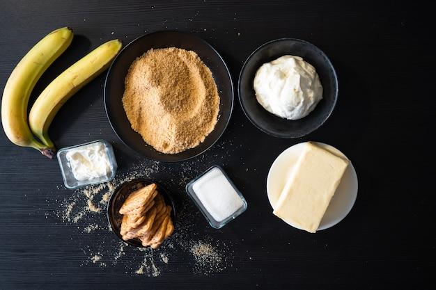 Ingrediënten voor een zandkoektaart met banaan en karamel, zwarte houten tafel in de keuken, producten bereid voor een heerlijk dessert met room, huisgemaakte gerechten