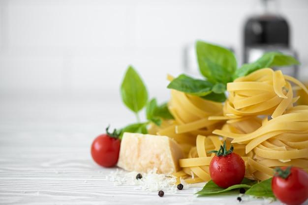 Ingrediënten voor fettuccine pasta met tomaten, kruiden en basilicum