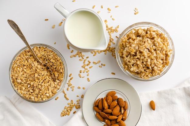 Ingrediënten voor gezond ontbijt - gerolde haver, melk en amandelen op wit