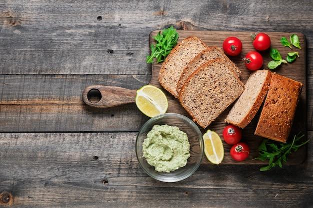 Ingrediënten voor gezonde sandwiches. gesneden huisgemaakt volkorenbrood, cherrytomaatjes, veldsla, rucola en avocado-guacamole.