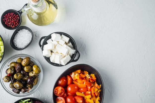 Ingrediënten voor griekse salade, op witte tafel, bovenaanzicht plat lag