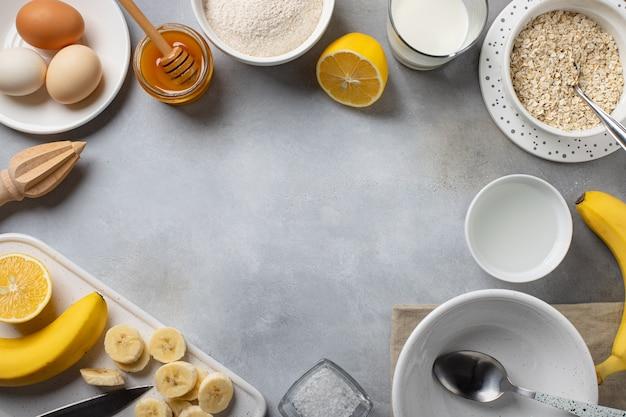 Ingrediënten voor heerlijke koken frame met banaan havermout pannenkoeken voedsel frame grijs betonnen oppervlak