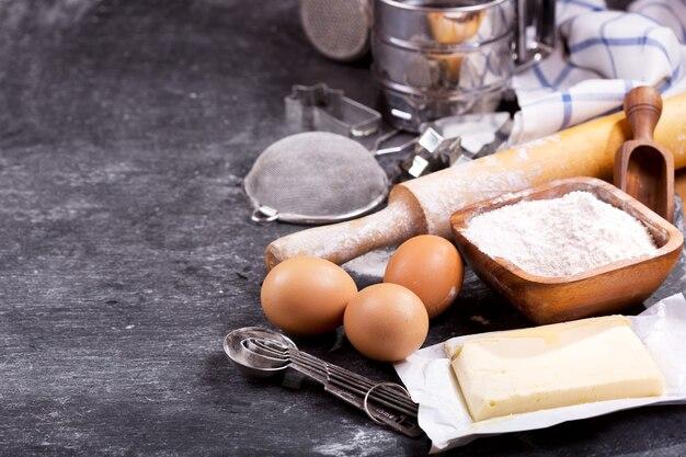 Ingrediënten voor het bakken: bloem, eieren, boter en keukengerei om te koken