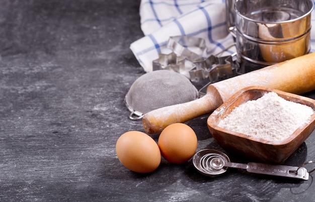 Ingrediënten voor het bakken: bloem, eieren en keukengerei om te koken