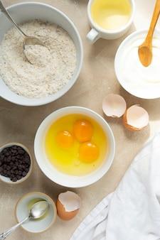 Ingrediënten voor het bakken, koken van dessert of gebak. bovenaanzicht, kommen met bloem, suiker, eieren, olie, chocoladeschilfers.