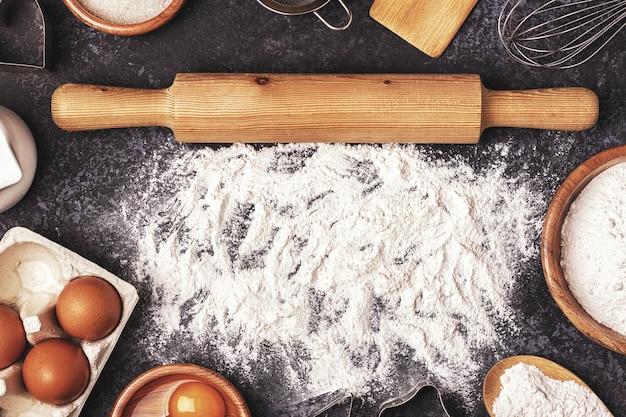 Ingrediënten voor het bakken met bloem, houten lepel en deegroller